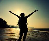 giovane donna a braccia aperte sulla spiaggia di alba Fotografie Stock