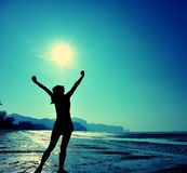 giovane donna a braccia aperte sulla spiaggia di alba Immagine Stock