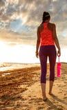 Giovane donna in buona salute in abiti sportivi sulla camminata della spiaggia Fotografia Stock