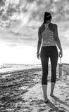 Giovane donna in buona salute in abiti sportivi sulla camminata della spiaggia Immagini Stock Libere da Diritti
