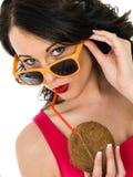 Giovane donna in buona salute attraente che beve da una noce di cocco fresca Immagine Stock