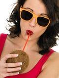 Giovane donna in buona salute attraente che beve da una noce di cocco fresca Fotografia Stock Libera da Diritti