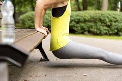 Giovane donna in buona salute che allunga prima della forma fisica e dell'esercizio in parco, concetto sano di stile di vita Immagine Stock