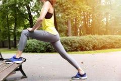 Giovane donna in buona salute che allunga prima della forma fisica e dell'esercizio in parco, concetto sano di stile di vita Fotografia Stock Libera da Diritti