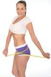 Giovane donna in buona salute che controlla la sua perdita di peso con una misura di nastro fotografie stock