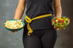 Giovane donna in buona salute che esamina alimento sano e non sano, provante ad operare la giusta scelta immagini stock libere da diritti
