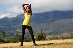 Giovane donna in buona salute che fa allungando esercizio Immagine Stock Libera da Diritti