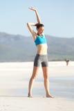 Giovane donna in buona salute che fa allungando esercizio alla spiaggia Fotografia Stock Libera da Diritti