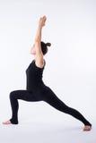 Giovane donna in buona salute che pratica equilibrando yoga di posizione del bastone su fondo bianco Fotografia Stock