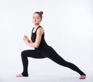 Giovane donna in buona salute che pratica equilibrando yoga di posizione del bastone su fondo bianco Fotografie Stock