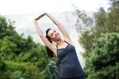 Giovane donna in buona salute che sorride e che allunga all'aperto Fotografie Stock Libere da Diritti