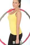 Giovane donna in buona salute che tiene una Bell e un hula-hoop muti Fotografie Stock Libere da Diritti