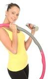 Giovane donna in buona salute che tiene una Bell e un hula-hoop muti Immagini Stock