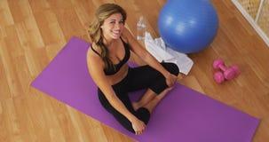Giovane donna in buona salute felice che sorride sulla stuoia di allenamento Immagini Stock