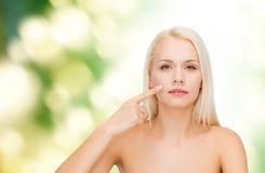 Giovane donna calma che indica alla sua guancia Immagine Stock