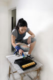Giovane donna capace che dipinge una parete immagini stock libere da diritti