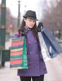 Giovane donna in cappello con i sacchetti della spesa multicolori fotografia stock libera da diritti