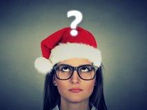 Giovane donna in cappello del Babbo Natale con il punto interrogativo Fotografie Stock