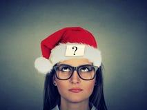 Giovane donna in cappello del Babbo Natale con il punto interrogativo Fotografia Stock