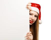 Giovane donna in cappello del Babbo Natale con la cartolina di Natale Immagine Stock