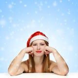 Giovane donna in cappello del Babbo Natale su fondo blu con la s di caduta Fotografia Stock