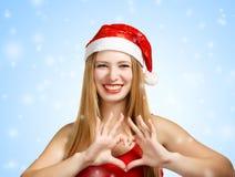 Giovane donna in cappello di Santa con forma del cuore Immagini Stock Libere da Diritti