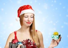 Giovane donna in cappello di Santa con gli attributi di natale ed il piccolo gi Fotografia Stock