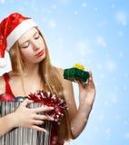Giovane donna in cappello di Santa con gli attributi di natale ed il piccolo gi Fotografie Stock Libere da Diritti
