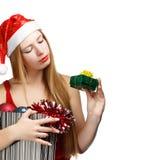 Giovane donna in cappello di Santa con gli attributi di natale ed il piccolo gi Immagini Stock