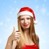 Giovane donna in cappello di Santa con i pollici su Immagini Stock