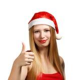 Giovane donna in cappello di Santa con i pollici su Fotografia Stock