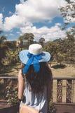 Giovane donna in cappello e vestito da estate che stanno sul balcone o terrazzo sopra bello Forest Landscape tropicale Fotografie Stock Libere da Diritti