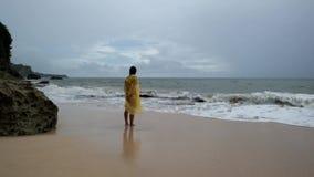 Giovane donna in cappotto di pioggia giallo sulla spiaggia in pioggia persistente in Bali Indonesia archivi video