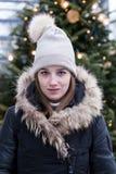 Giovane donna in cappotto nero di inverno sistemato pelliccia con l'albero di Natale acceso nel fondo molle del fuoco fotografie stock libere da diritti