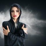 Giovane donna in cappuccio nero con la traversa Fotografia Stock