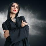 Giovane donna in cappuccio nero con la traversa Immagine Stock