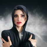 Giovane donna in cappuccio nero con la traversa Immagine Stock Libera da Diritti
