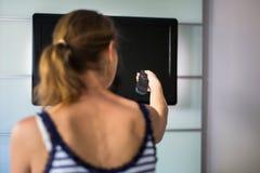 Giovane donna a casa che guarda TV, canale cambiante Fotografia Stock