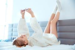 Giovane donna a casa che pone i vantaggi sulla parete a letto che indossa le immagini del selfie del maglione Fotografia Stock Libera da Diritti