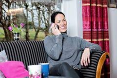 Giovane donna a casa che si siede sul sofà e sulla chiamata Fotografia Stock Libera da Diritti