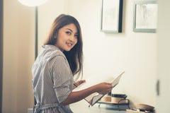 Giovane donna a casa che si siede sulla sedia davanti alla finestra che si rilassa in suo libro di lettura del salone Fotografie Stock Libere da Diritti