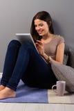 Giovane donna a casa con la compressa Immagine Stock Libera da Diritti