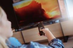 Giovane donna a casa nel salone che guarda programma della TV immagini stock