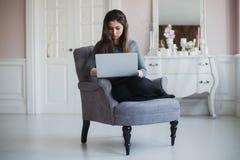 Giovane donna a casa nella poltrona che si rilassa nella sua stanza lliving con il computer portatile Fotografia Stock Libera da Diritti