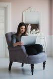 Giovane donna a casa nella poltrona che si rilassa nella sua stanza lliving con il computer portatile Fotografie Stock Libere da Diritti