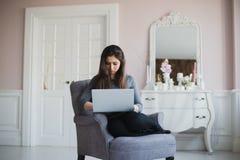 Giovane donna a casa nella poltrona che si rilassa nella sua stanza lliving con il computer portatile Immagini Stock Libere da Diritti