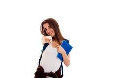 Giovane donna castana adorabile dello studente con lo zaino blu sulla sua spalla e cartella per i taccuini in mani che esaminano Immagini Stock