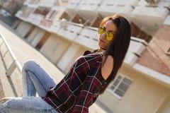 Giovane donna castana alla moda nella seduta degli occhiali da sole Fotografia Stock