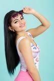 Giovane donna castana attraente in canottiera sportiva rosa su fondo blu Ragazza di Smilling in occhiali da sole Immagine Stock