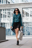 Giovane donna castana attraente che cammina sulla vita di città della via Immagine Stock
